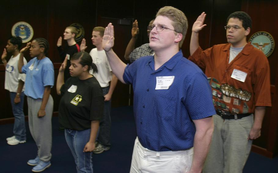 """Army inductees, including Josh Anderson, center, take the oath of enlistment at the Federal Building in Richmond, Va., Thursday, April 3, 2003. Anderson said at the time that his resolve to join the Army during wartime was """"stronger than ever."""""""