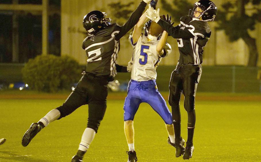 Zama American receivers Keshawn McNeill and Pierce Ingram and Yokota defensive back Michael Kasten go up for the ball.