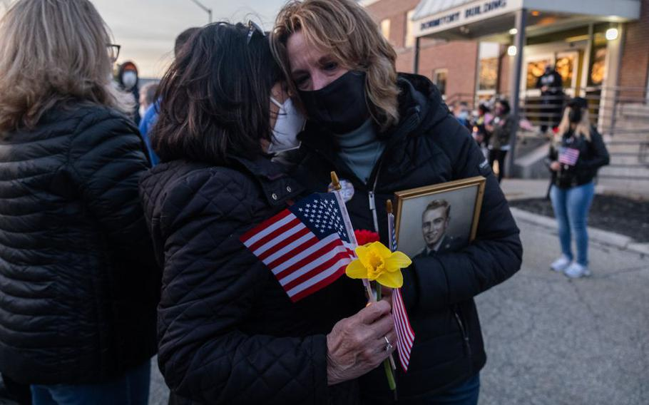 Roberta Weber-Twining (left) hugs Cheryl Turgeon during a vigil at the Soldiers' Home in Holyoke, Mass., on Tuesday, March 30, 2021. Turgeon's father, Korean War veteran Dennis Thresher, survived the coronavirus outbreak at the Soldiers' Home in 2020 but died in January 2021. Weber-Twining's husband, Tim, is currently living at the Home.