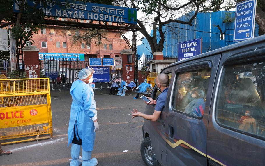 Health workers turn away a vehicle at the main entrance of the Lok Nayak Jaiprakash Hospital in New Delhi on April 25, 2021.