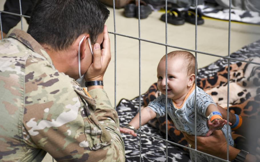 U.S. Army 1st Lt. Daniel Duncan plays with an Afghan child waiting for a flight to the U.S. in a hangar at Ramstein Air Base in Germany on Wednesday, Sept. 1, 2021.
