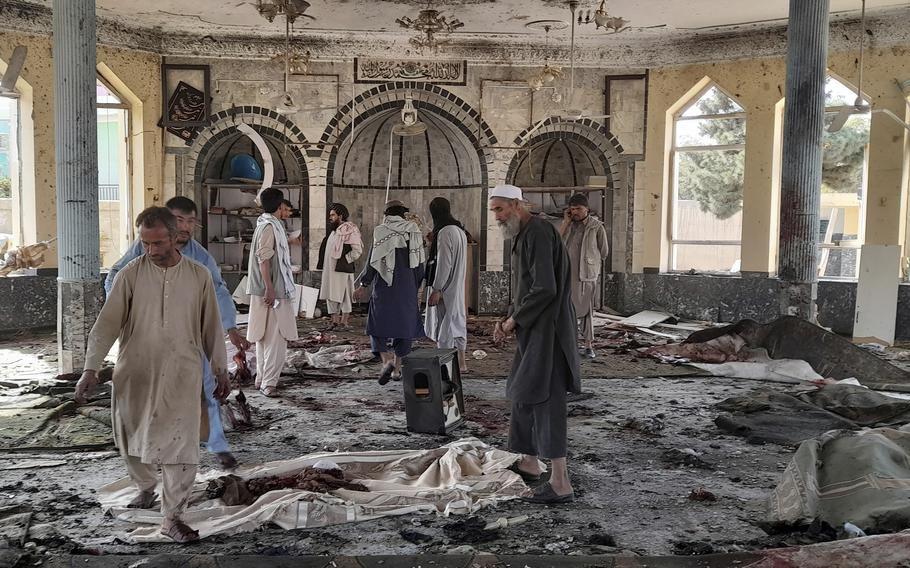 People view the damage inside of a mosque following a bombing in Kunduz, province, northern Afghanistan, Friday, Oct. 8, 2021.