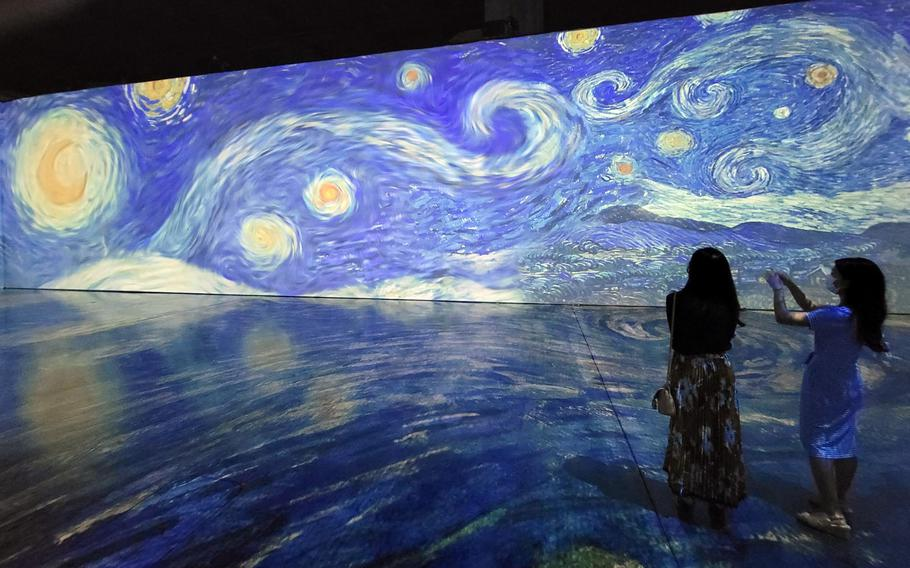 """Visitors at Beyond Van Gogh: The Immersive Experience at the Honolulu Convention Center snap photos of the artist's iconic painting, """"The Starry Night."""""""