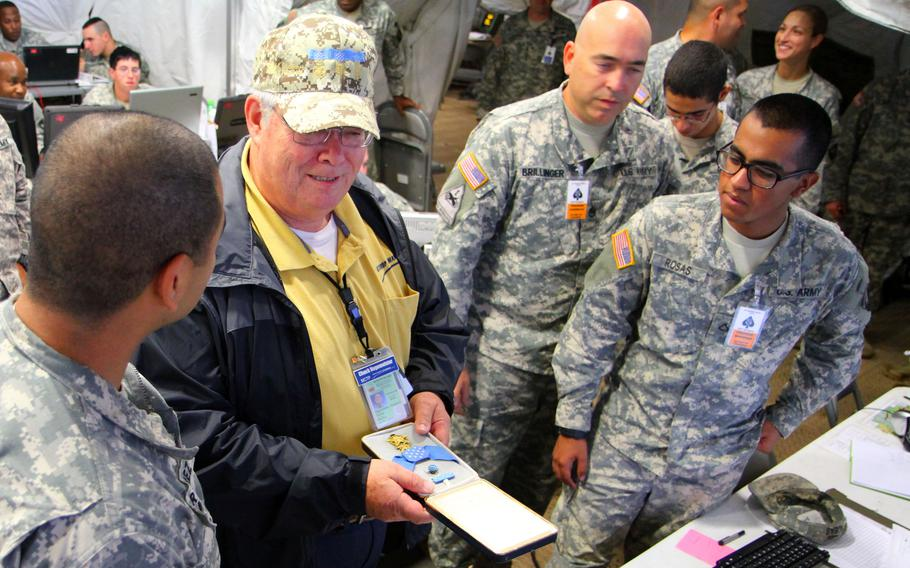 Medal of Honor recipient Charles Hagemeister shows his medal to soldiers working a night shift at Fort Campbell, Ky., Sept. 17, 2012.  Hagemeister, a former Army medic who earned the honor during the Vietnam War, died Wednesday, May 19, 2021.