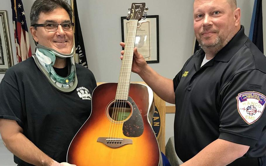 An Air Force veteran identified as Gordon M., left, receives a free guitar after completing 10 free lessons from Guitars4Vets, a Wisconsin-based charity that helps veterans overcome post-traumatic stress disorder through music.