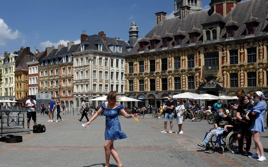 A woman dances by a cafe terrace in Lille, northern France, French tourism seeks new boost with Disneyland reopening. In France, authorities said it's no longer always mandatory to wear masks outdoors.