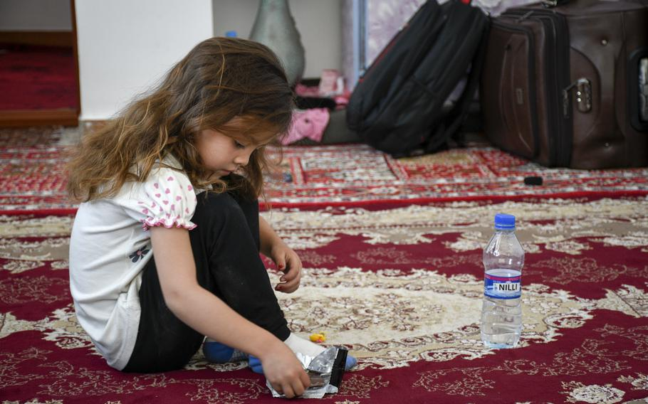 Zainab Asadi, 5, snacks on chocolate May 31, 2021, in the home where she and her family hid for six months. Her father, Mohammed Naiem Asadi, said he moved his family into hiding after his superiors in the Afghan air force became angry that he received permission to leave the country for America.