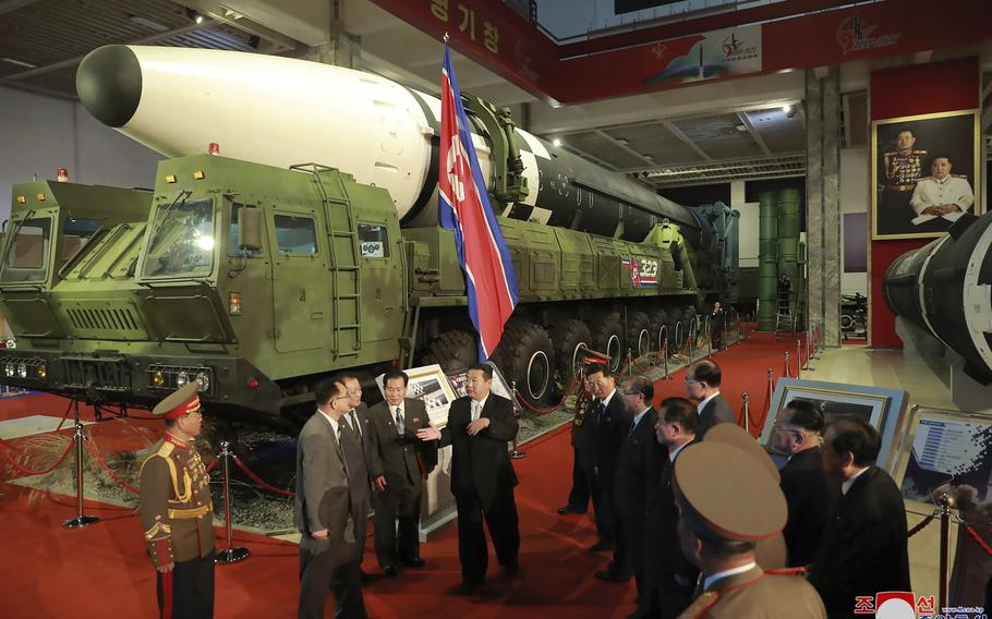 """In this photo provided by the North Korean government, North Korean leader Kim Jong Un, center, speaks in front of what the North says an intercontinental ballistic missile displayed at an exhibition of weapons systems in Pyongyang, North Korea, Monday, Oct. 11, 2021. Independent journalists were not given access to cover the event depicted in this image distributed by the North Korean government. The content of this image is as provided and cannot be independently verified. Korean language watermark on image as provided by source reads: """"KCNA"""" which is the abbreviation for Korean Central News Agency."""