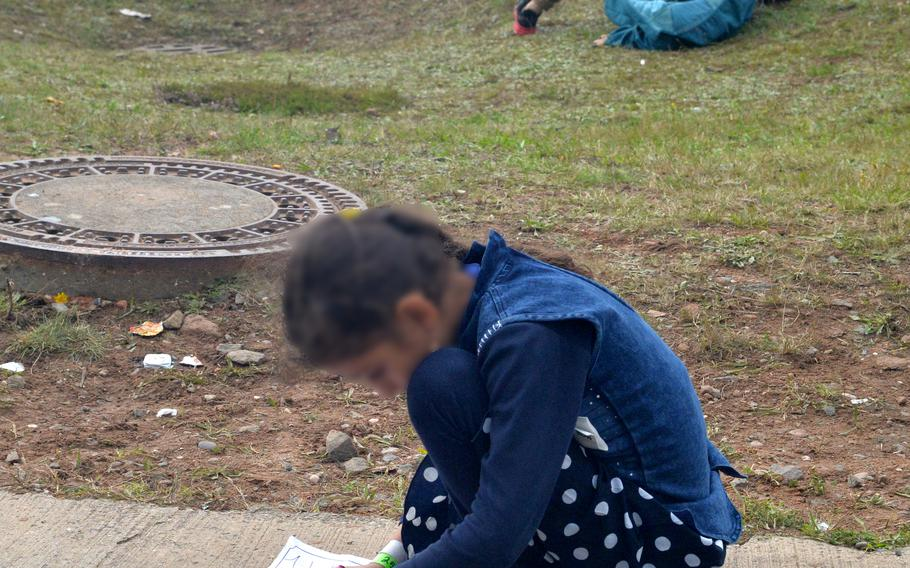 An Afghan girl draws while two boys play on the grass at Rhine Ordnance Barracks in Kaiserslautern, Germany, Aug. 30, 2021. More than 3,000 evacuees from Afghanistan have been housed at the Army installation, which is taking some of the pressure off Ramstein Air Base, where around 24,000 evacuees have arrived in the past two weeks.