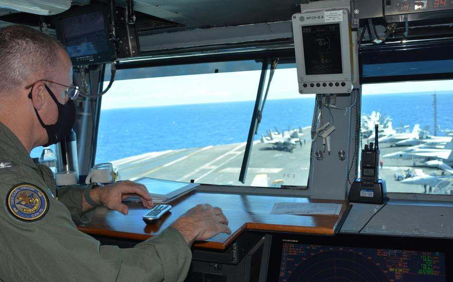 Capt. P. Scott Miller, commander of the aircraft carrier USS Carl Vinson, surveys aircraft on the ship's bow as it steams north of Oahu, Hawaii, on Aug. 14, 2021.