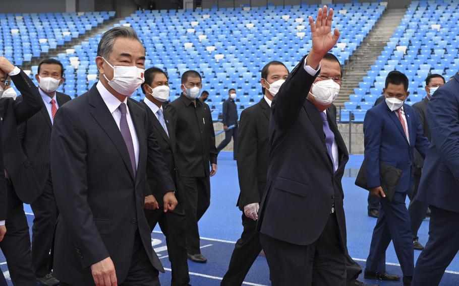 Chinese Foreign Minister Wang Yi, front left, accompanied by Cambodian Prime Minister Hun Sen, front right, walks around during a tour of the Morodok Techo National Stadium as it was handed over to the Cambodian organizing committee of the Southeast Asian Games in Phnom Penh, Cambodia, Sunday, Sept. 12, 2021. Wang is visiting Cambodia, where he met with Hun Sen and other officials to discuss COVID-19 and other regional issues.