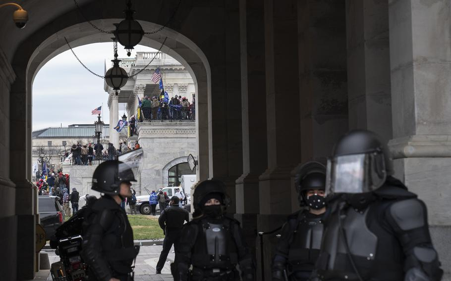 U.S. Capitol Police, in riot gear, stand in a carriageway at the Capitol in Washington on Jan. 6.