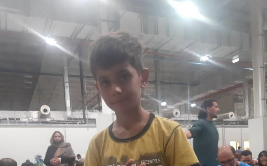 Noman Mujtaba flashes the peace sign from a hangar, Aug. 21, 2021, at Al Udeid Air Base in Qatar, in a photo sent to his adoptive father Bahaudin Mujtaba after Noman was evacuated safely from Kabul, Afghanistan, days earlier.