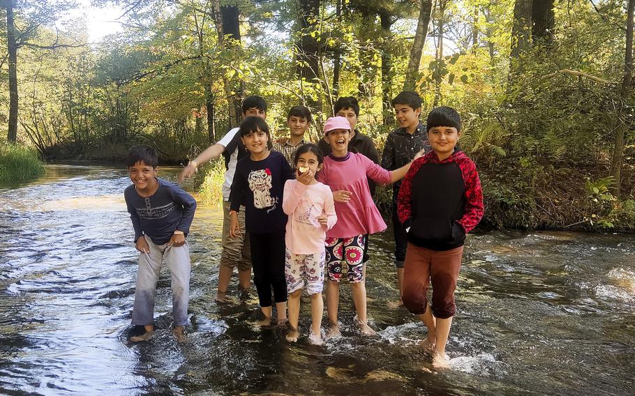 Afghan children play in a stream at Fort McCoy, Wis., Sept. 28, 2021.