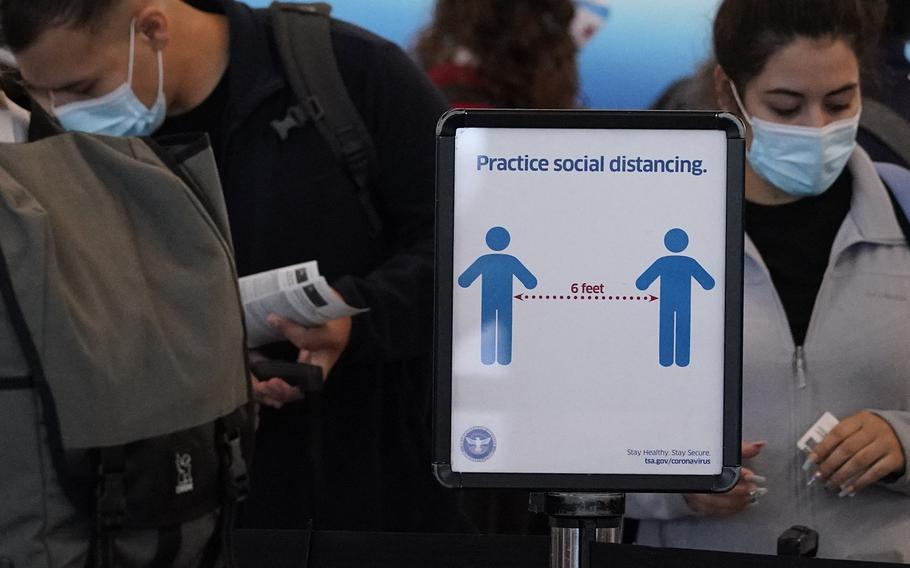 Travelers wait to check-in for their flights as a sign reminding travelers to social distance is displayed in Terminal 3 at O'Hare International Airport in Chicago, Friday, July 2, 2021.