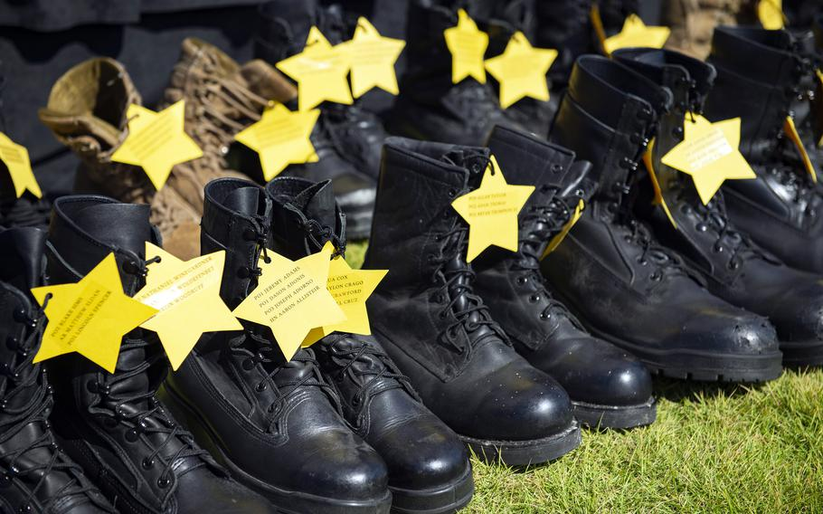 Boots representing fallen sailors are displayed during a Bells Across America ceremony at Yokosuka Naval Base, Japan, Thursday, Sept. 23, 2021.