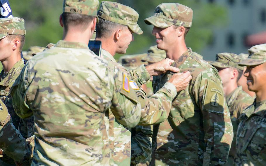 Army Maj. Gen. David Hodne, the Army's infantry commandant, pins jump wings on a soldier graduating the Army's Basic Airborne Course at Fort Benning, Ga. on Friday, May 21, 2021. The ceremony was the first public graduation for the Army's Airborne School since the coronavirus pandemic began more than one year ago.