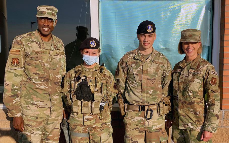 Chief Master Sgt. Nicolas Taylor, 90th Missile Wing command chief, Airman Suzanne Pedro, and Airman 1st Class Frank Shaw, both from 90th Security Forces Squadron, and Col. Catherine Barrington, 90 MW commander, pose for a photo on F.E. Warren Air Force Base, Wyoming, July 7, 2021. The Airmen were coined by wing leadership in recognition of excellence while performing their duties. Their actions in defending the base directly contributed to the capture of an individual with active arrest warrants and the recovery of a missing child.