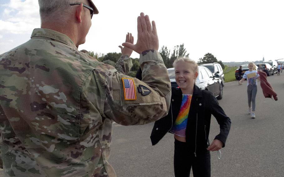 Maj. Mark Fitzgerald of the Texas National Guard high-fives a Dutch girl as she and her classmates from De Oversteek school arrive on Sept. 20, 2021, for a ceremony to mark the 77th anniversary of the crossing the Waal River in Nijmegen, Netherlands, during Operation Market Garden in World War II.