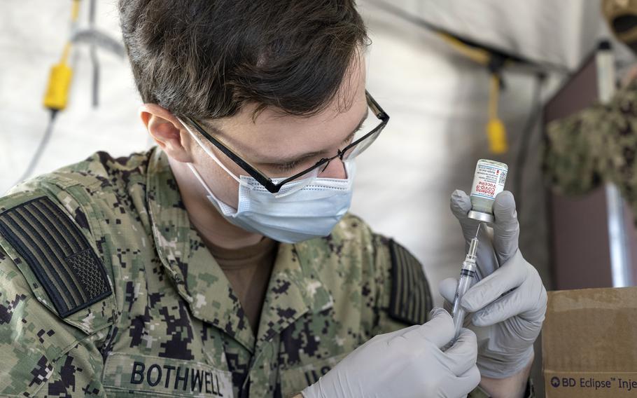 A Navy hospitalman fills a syringe with the Moderna COVID-19 vaccine earlier this year at Naval Hospital Okinawa.