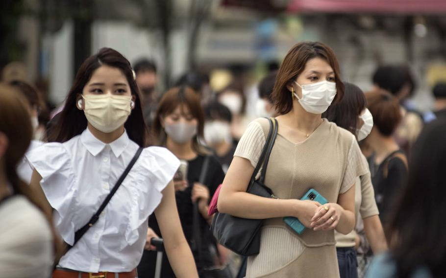 Commuters walking near Shinjuku Station wear masks to guard against the coronavirus early this summer in central Tokyo.