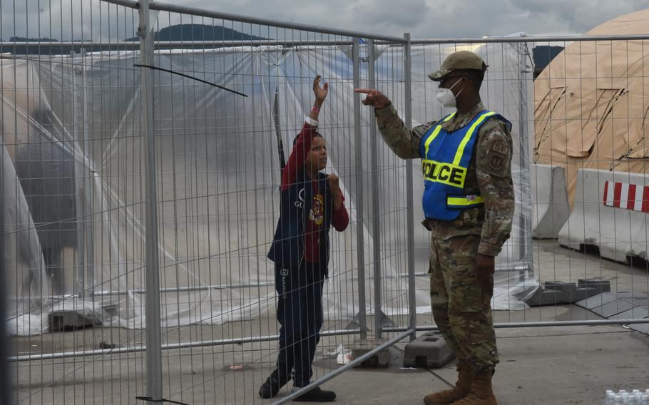 A boy talks through the fence with a security forces airman at a temporary living facility set up for evacuees from Afghanistan on Ramstein Air Base, Germany, Aug. 23, 2021.
