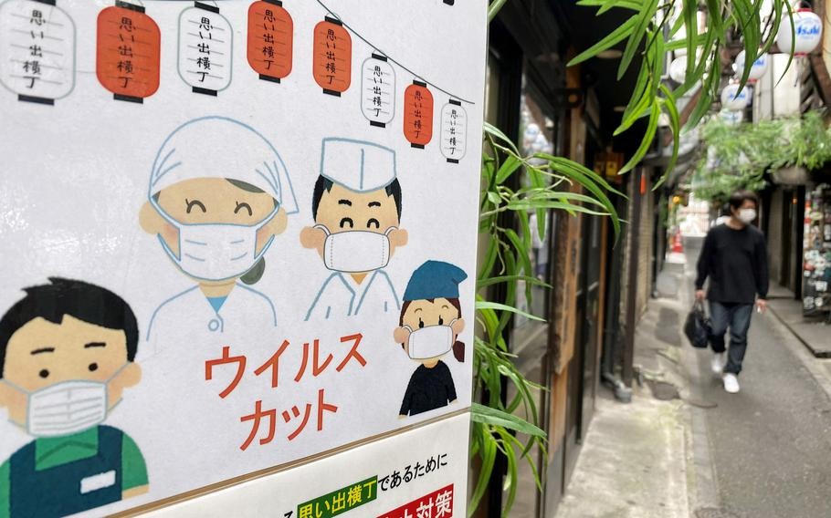 A sign informs customers that workers are taking coronavirus precautions at Omoide Yokocho, an alleyway lined with food stalls in Shinjuku, Tokyo, Sunday, June 13, 2021.