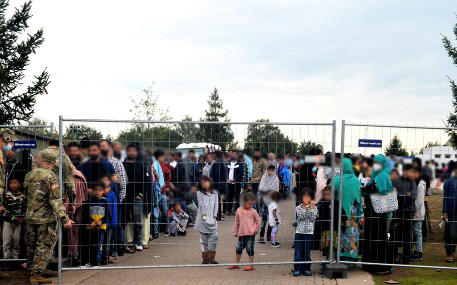 Afghan evacuees wait by fencing on Rhine Ordnance Barracks in Kaiserslautern, Germany, for the evening meal, Aug. 30, 2021. The Army installation was transformed in four days to help nearby Ramstein Air Base temporarily house thousands of Afghans who have been airlifted out of Kabul since the Taliban seized control in Afghanistan.