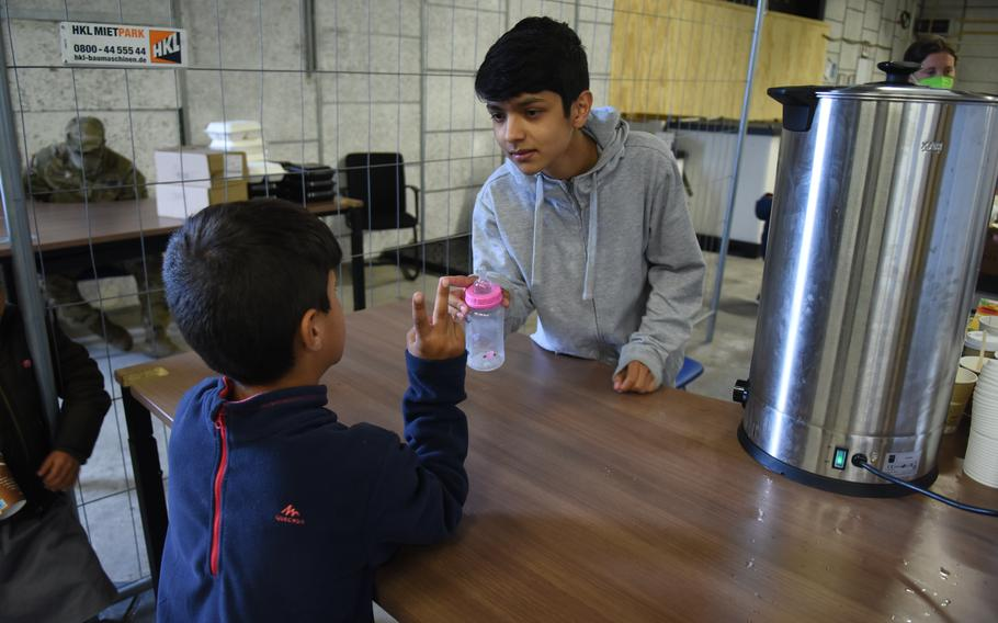 Erfan Ahmadi, 14, takes requests for formula and tea while volunteering at Rhine Ordnance Barracks, Germany, on Sept. 20, 2021. Ahmadi and his family are evacuees from Afghanistan. He speaks Dari, Pashto and English and is one of several Afghan teens who translate for American volunteers at the stations where baby formula and hot tea are served.