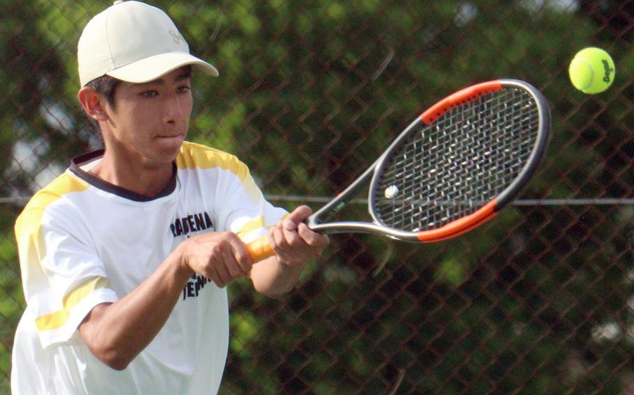 Kadena's Nathan Asato hits a backhand shot during Wednesday's Okinawa doubles tennis matches. Asato and his partner Iain Stanley beat Kubasaki's Canaan Jones and Jacy Fisk 8-6.