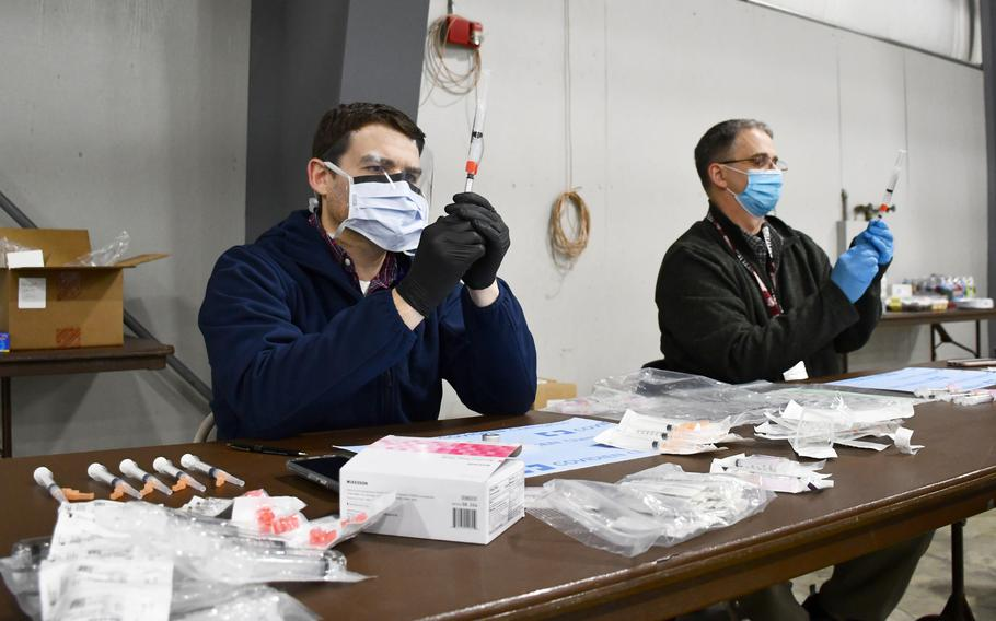 Pharmacists CJ Ludwig, front, and Chris Elizagaray, back, pull doses of the coronavirus vaccine from vials at a Department of Veterans Affairs vaccination clinic in Kalispell, Montana, on Tuesday, March 2, 2021.