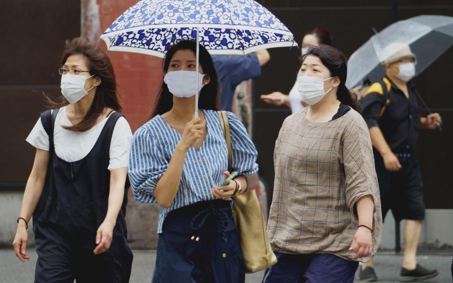 Pedestrians in central Tokyo wore masks as protection agains the coronavirus on Aug. 13, 2021.