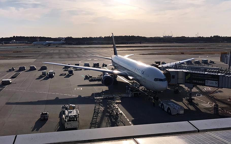 A U.S.-bound plane is parked at a gate at Narita International Airport in Japan in 2019. The Defense Department will roll out a replacement to the Defense Travel System over the next three years.
