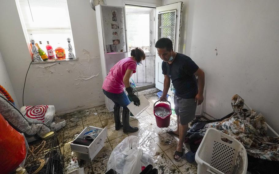 Residents of Peck Ave in the Flushing neighborhood of the Queens borough of New York use buckets to remove water from their basement apartment, Thursday, Sept. 2, 2021, in New York.