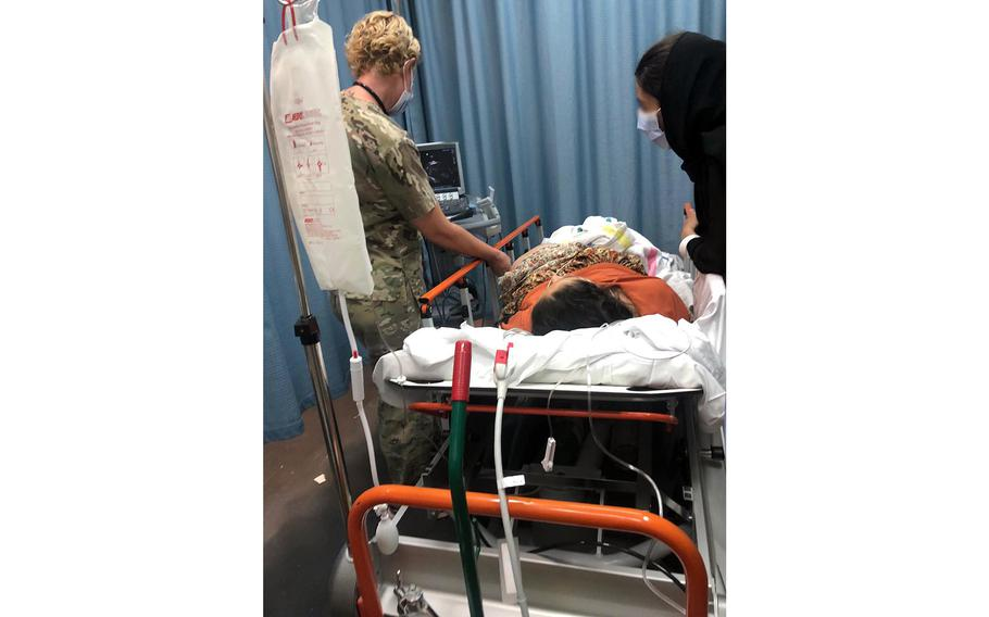 Dr. (Maj.) Elaina Wild, 379th Expeditionary Medical Group chief medical officer, examines an evacuee from Afghanistan before she gives birth at Al Udeid Air Base, Qatar, Aug. 28, 2021.