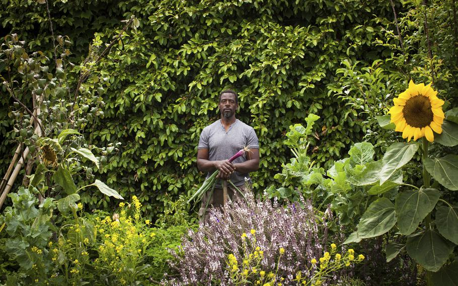 """Ron Finley stands in an urban garden in Los Angeles. In some of the poorest neighborhoods in major cities, a dearth of fresh produce has created so-called """"food deserts,"""" along with high rates of diabetes and malnutrition. The urban gardening movement is trying to change that. Charismatic community leaders like Ron Finley in LA have argued for years that growing your own food is empowering."""