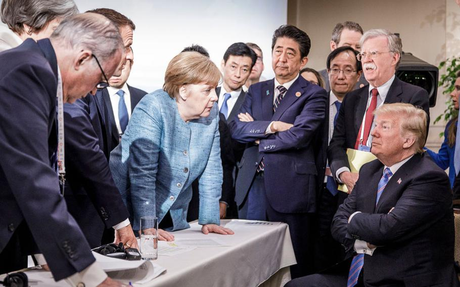 German Chancellor Angela Merkel deliberates with US president Donald Trump on the sidelines of the official agenda on the second day of the G7 summit on June 9, 2018 in Charlevoix, Canada.