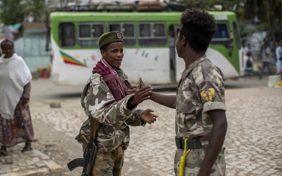 Fighters loyal to the Tigray People's Liberation Front greet each other on the street in the town of Hawzen, then-controlled by the group, in the Tigray region of northern Ethiopia, on May 7, 2021. The rural town is a microcosm of the challenge facing Prime Minister Abiy Ahmed - and a warning that the war here is unlikely to end anytime soon.