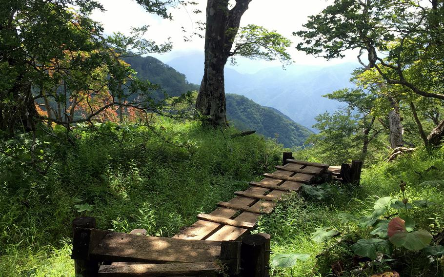 A wooden walkway seems to lead to distant peaks from the summit of  Mount Hinokiboramaru in Kanagawa prefecture, Japan.