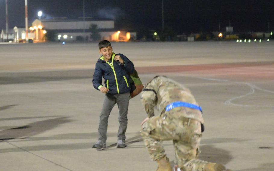 An Afghan boy breaks away from the group of evacuees he is traveling with on Saturday, Oct. 9, 2021, to fist-bump an airman at Ramstein Air Base, Germany.