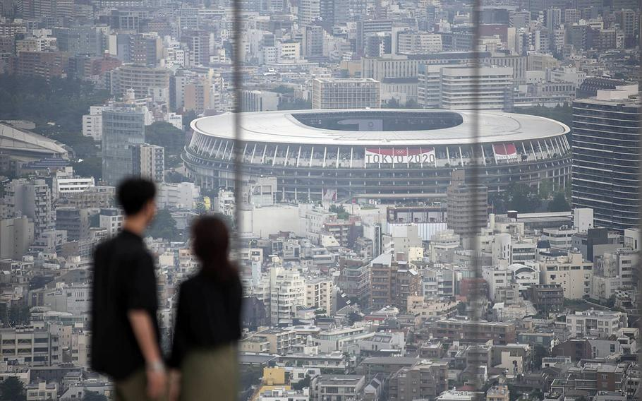 People check out Olympic Stadium from an observation deck in central Tokyo, Tuesday, July 13, 2021.