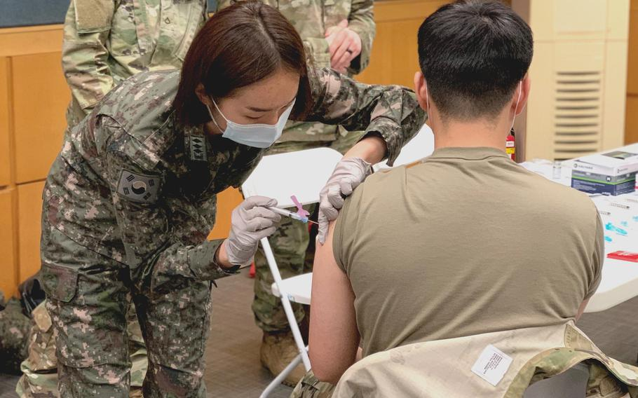 South Korean army Capt. Yeon Ju Oh administers a Moderna coronavirus vaccine to a Korean Augmentation to the U.S. Army soldier at Yongsan Garrison, South Korea, on Feb. 25, 2021.