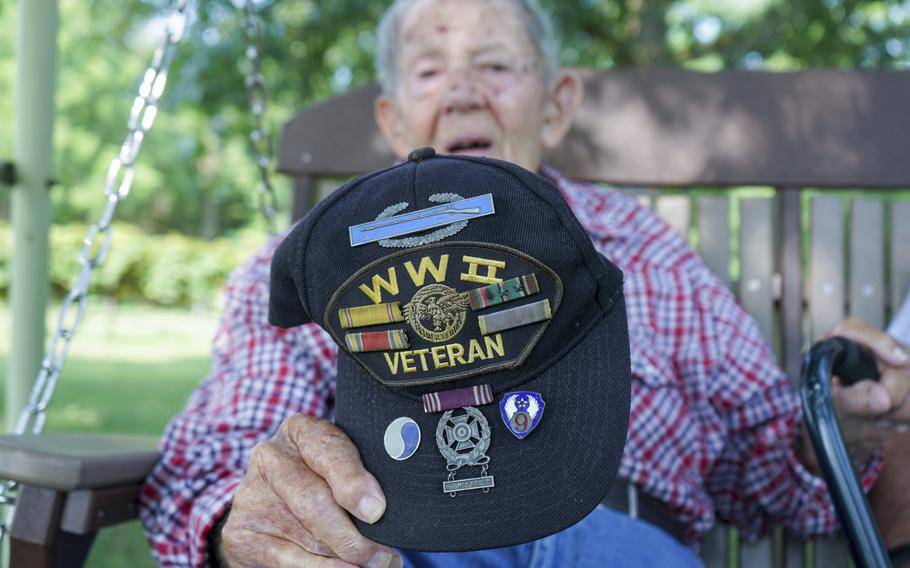 Beverly Salyards holds up his World War II veteran hat, adorned with several service ribbons and badges he earned during his time in the U.S. Army while talking about his experiences at Vietnam veteran Larry Ritchie's home in Rockingham County, Va.