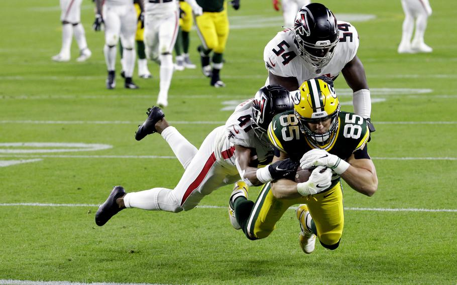 Green Bay Packers' Robert Tonyan (85) goes in for a touchdown as he is tackled by Atlanta Falcons' Sharrod Neasman (41) and Foye Oluokun (54) during the first half of an NFL football game, Monday, Oct. 5, 2020, in Green Bay, Wis. (AP Photo/Mike Roemer)