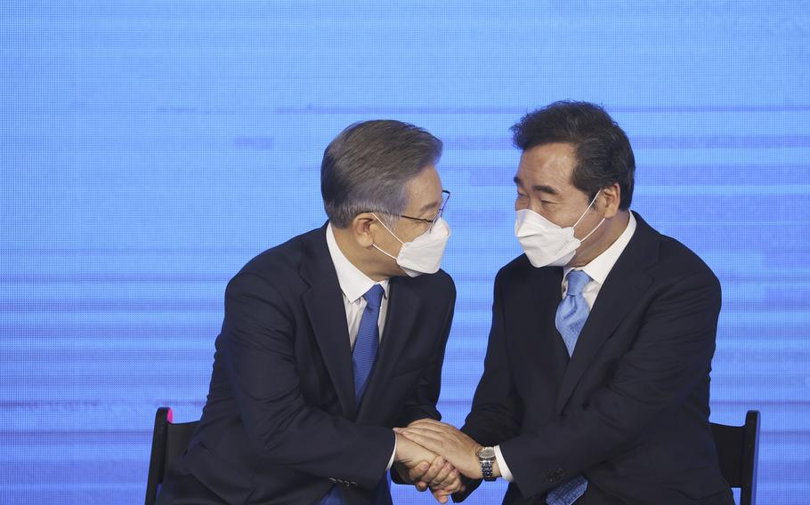 Gyeonggi Gov. Lee Jae-myung, left, elected as the ruling Democratic Party's candidate for next year's presidential election, shakes hands with former Prime Minister Lee Nak-yon after winning the party's final race to decide on the presidential candidate in Seoul, South Korea, Sunday, Oct. 10, 2021.