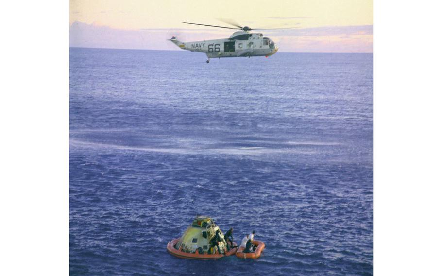 """A U.S. Navy Sea King helicopter arrives to recover the Apollo 10 astronauts, seen entering a life raft, as the Command Module """"Charlie Brown"""" floats in the South Pacific."""