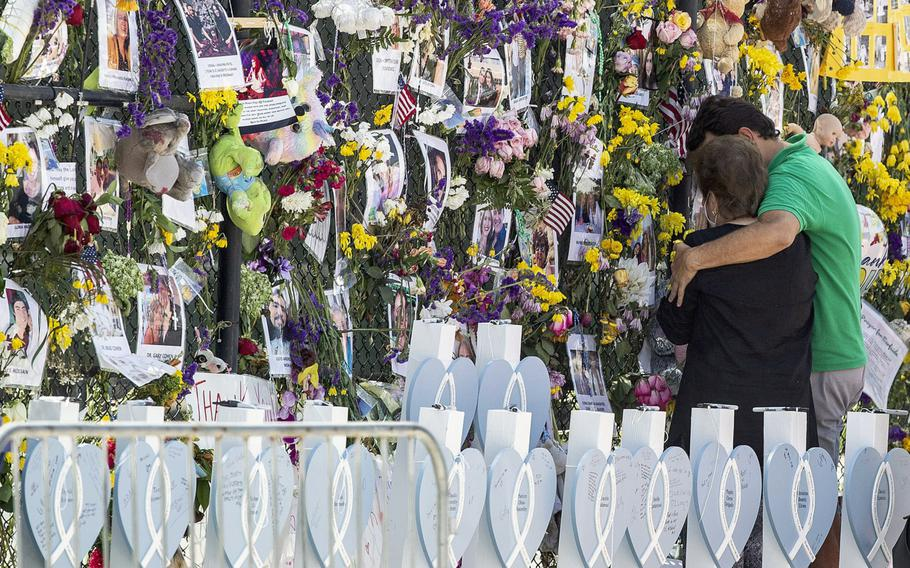 People mourn at the memorial wall for the victims of the Champlain Towers South collapse, in Surfside, Fla., on July 8, 2021.