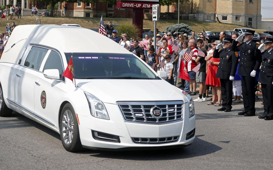 A hearse carrying the body of Marine Corps Cpl. Humberto Sanchez pauses during his funeral procession on Sunday, Sept. 12, 2021, in Logansport, Ind. Sanchez was among 13 U.S. service members killed in a suicide bombing during the U.S.-run evacuation at Afghanistan's Kabul airport on Aug. 26.