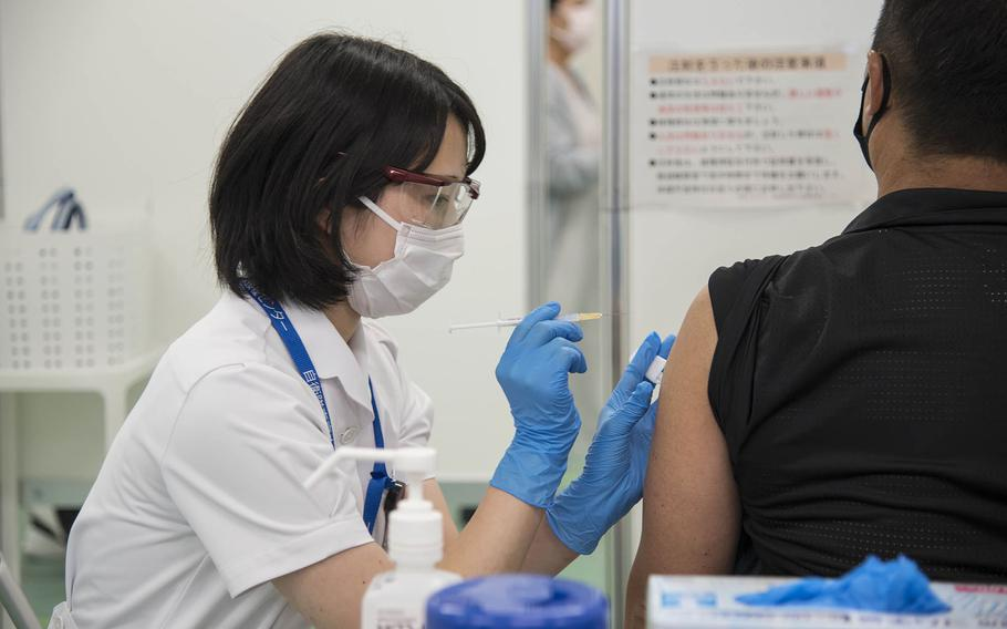 A medical worker with the Japan Ground Self-Defense Force injects a patient with the Moderna COVID-19 vaccine during a mass shot clinic in Otemachi, Tokyo, June 9.