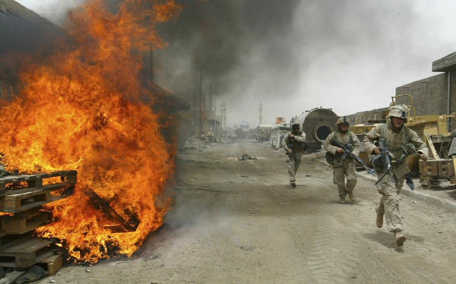 In this April 30, 2004, file photo, U.S. Marines burn their fortifications on front line positions in Fallujah, Iraq, before pulling out of the city.